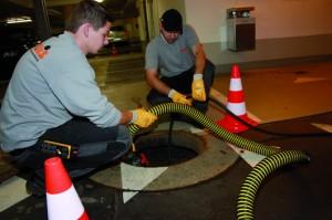 Der schwarze Schlauch mit Rotationsdüse spült, der gelbe saugt, im Hintergrund (r.) Mitarbeiter des Betreibers OPG