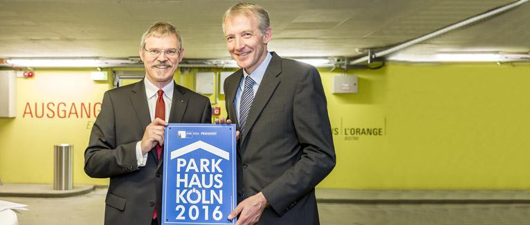 Dr. Ulrich S. Soénius, stellvertretender Hauptgeschäftsführer der IHK Köln (l.), überreicht die Plakette an Sebastian Emunds, Geschäftsführer der Rheinland Kultur GmbH, die das Sieger-Parkhaus im Köln-Triangle betreibt.
