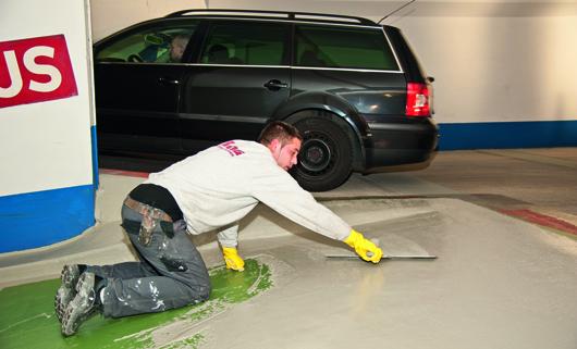 Der Mitarbeiter zieht mit dem Flächenspachtel den hoch abriebfesten und rutschfesten Strukturbelag auf.